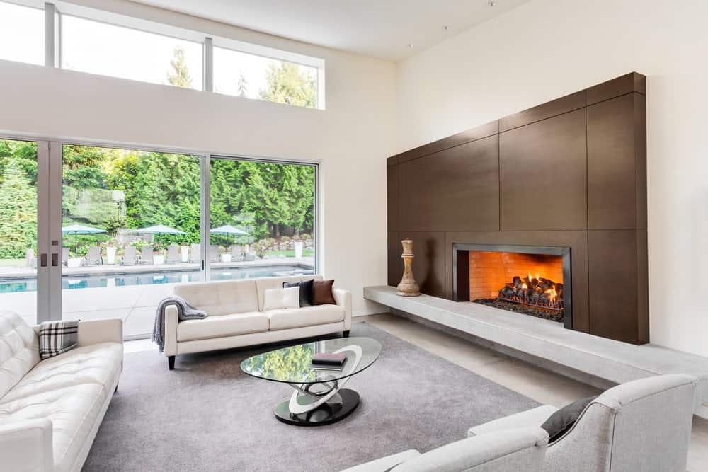 A spacious living room with white walls and a large gray rug along with white couches and a large fireplace.