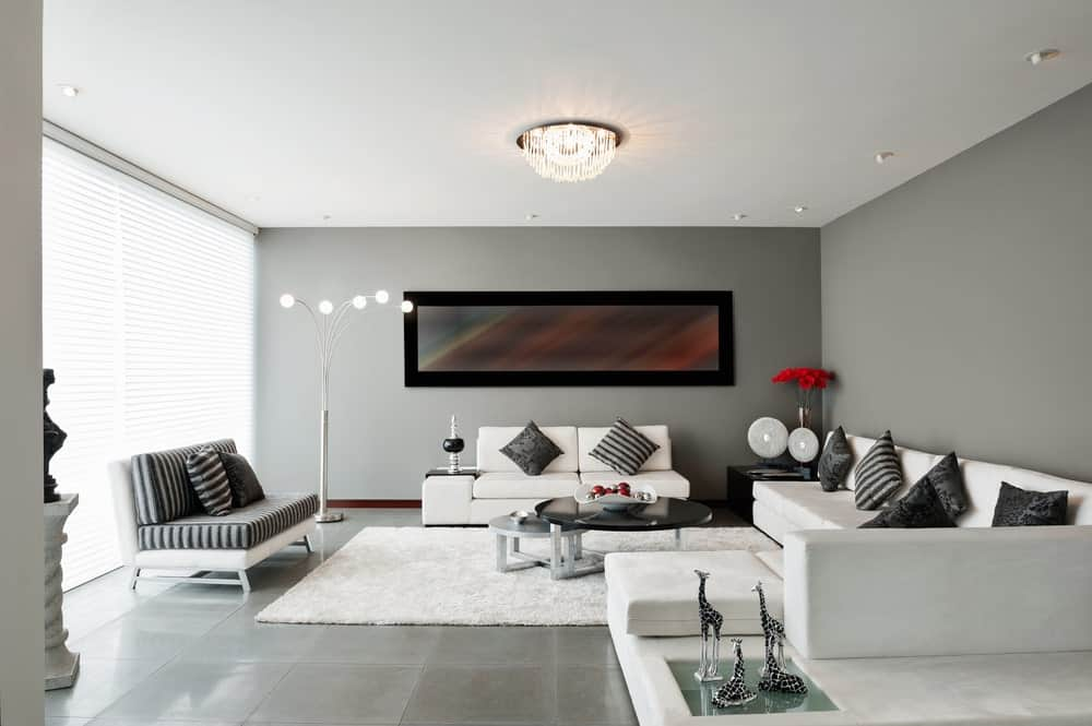 A spacious living room with gray walls and gray flooring. There's a white couch along with a gorgeous flush lighting.