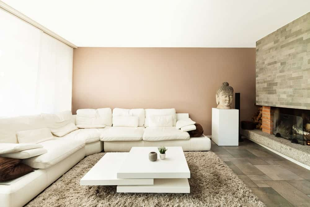 This living room offers a large white sofa set paired with a white center table along with a fireplace.