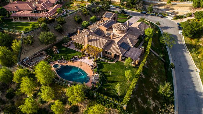 The aerial view of the mansion showcase the beautiful house structure and landscaping along with the gorgeous outdoor space.
