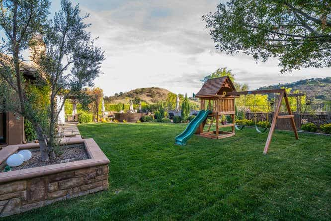 The backyard features a children's playground on a healthy lawn.