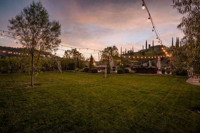 Backyard view of the mansion during the dusk, showcasing the beauty of the landscaping and lawn.
