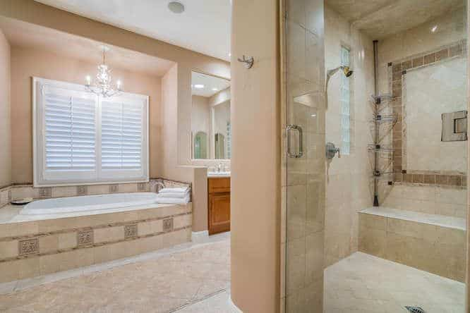 This master bathroom boasts a drop-in tub and a walk-in shower. It has classy tiles floors and lighted by fabulous ceiling lights.