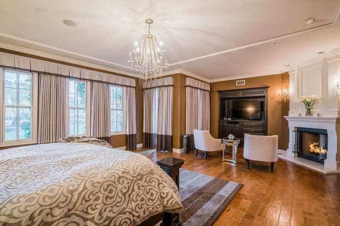 A dark wood bed faces the television and white fireplace in this primary bedroom with wood plank flooring and glazed windows covered in lovely draperies and valences.