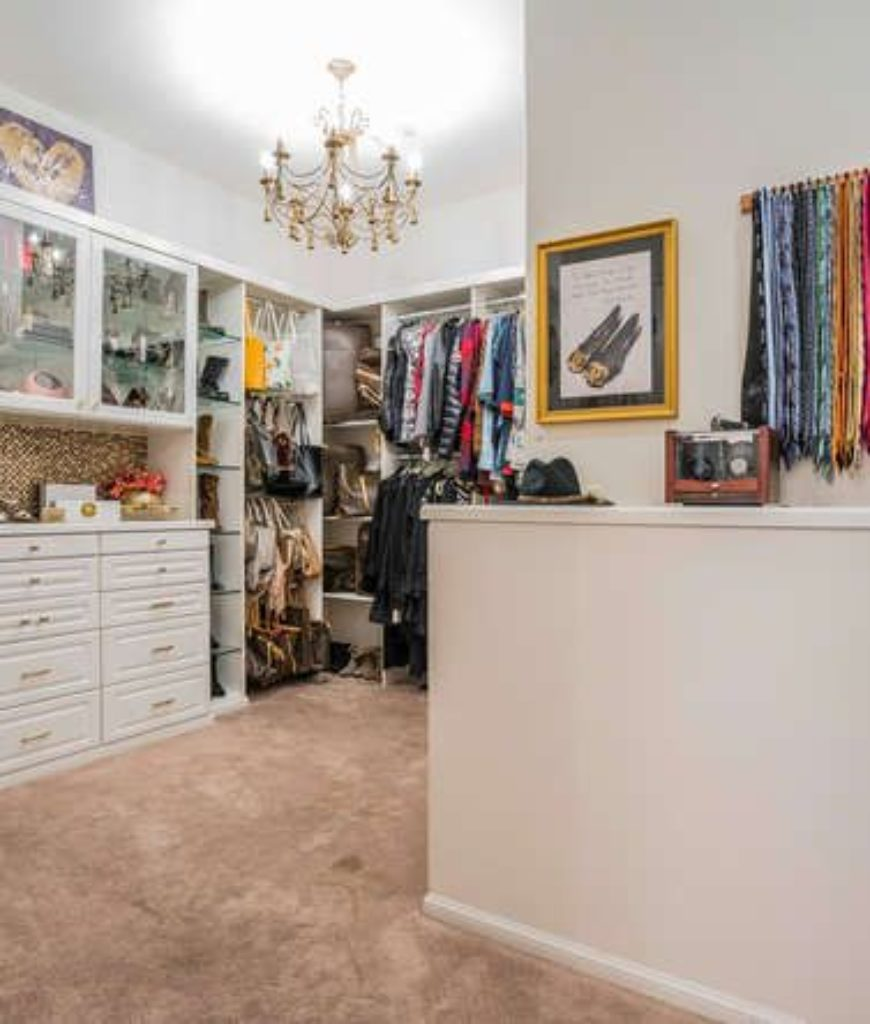The closet offers multiple storage, cabinets and drawers. White walls look perfect with the chandelier.