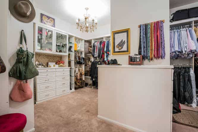 Classy bedroom closet featuring white walls and cabinetry along with carpet flooring and elegant chandelier lighting.