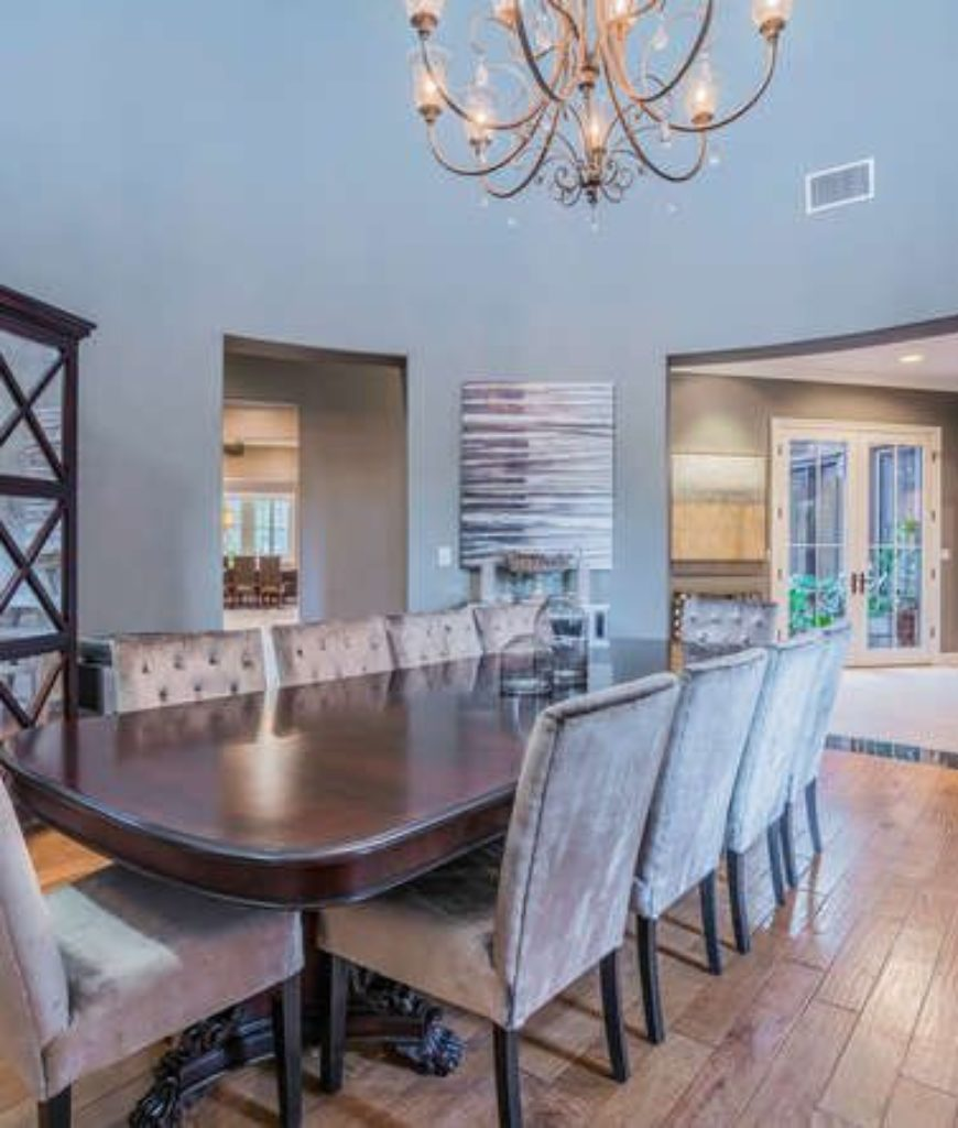 The dining room looks simple with its hardwood flooring and dining set. Chandelier lights up the room.
