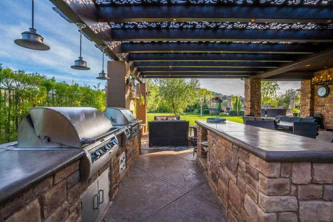 This outdoor kitchen features a stylish stone bricks-made bar counters. the center island offers a wide space for drinking or eating.