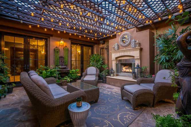 The mansion boasts an outdoor living space with a nice sofa set on a stylish rug and a fireplace surrounded by healthy plants.