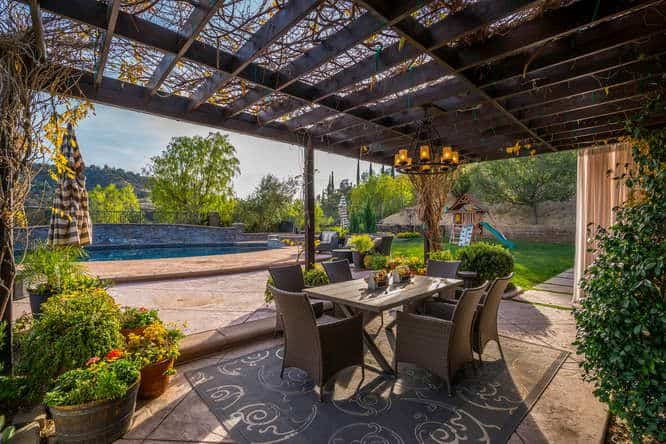 Outside, a pergola offering a nice dining spot sits just beside the swimming pool.