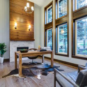 Luxury home office with high ceilings, huge windows, fireplace wood flooring.