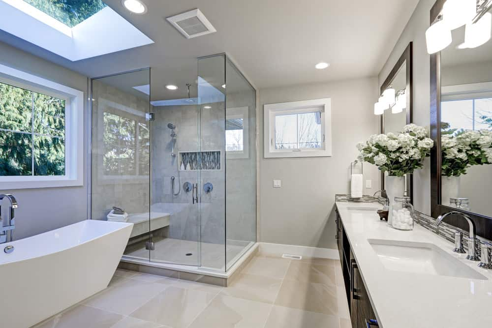 Large primary bathroom with a walk-in shower and a freestanding tub. The skylight is placed just above the bathtub. The room also features double sink lighted by wall lights.