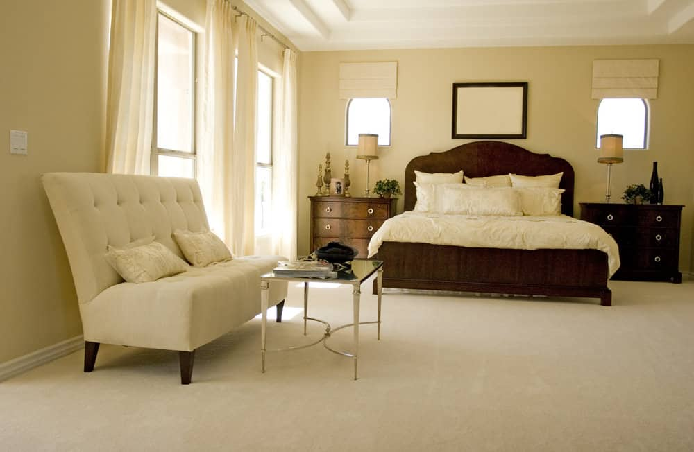 Spacious master bedroom with armless sofa sitting area and a classy glass top table set on the room's carpet floors.