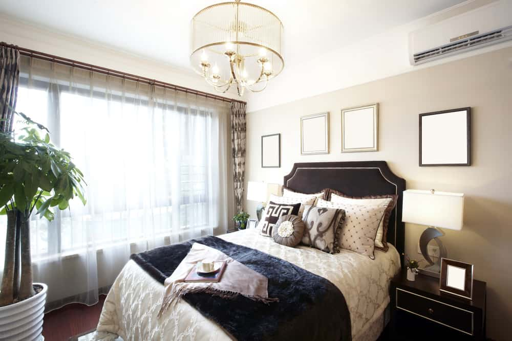 Stylish master bedroom with chandeleir light and curtains on bedroom with light beige walls.