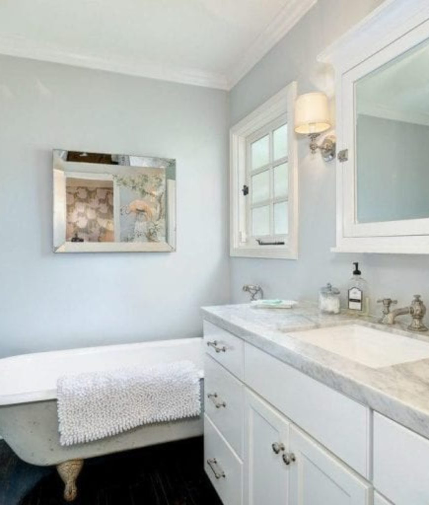 The bathroom offers a freestanding soaking tub and a walk-in shower along with a sink equipped by marble countertop.