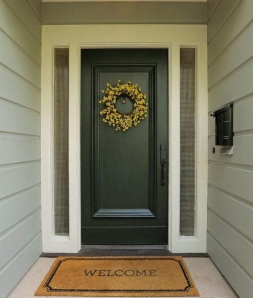 The house's entryway looks simple yet special with its dark hardwood door.