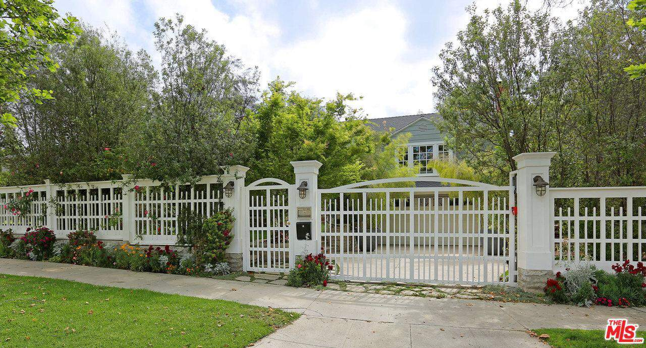 The house is protected by a wide white iron fence gate.
