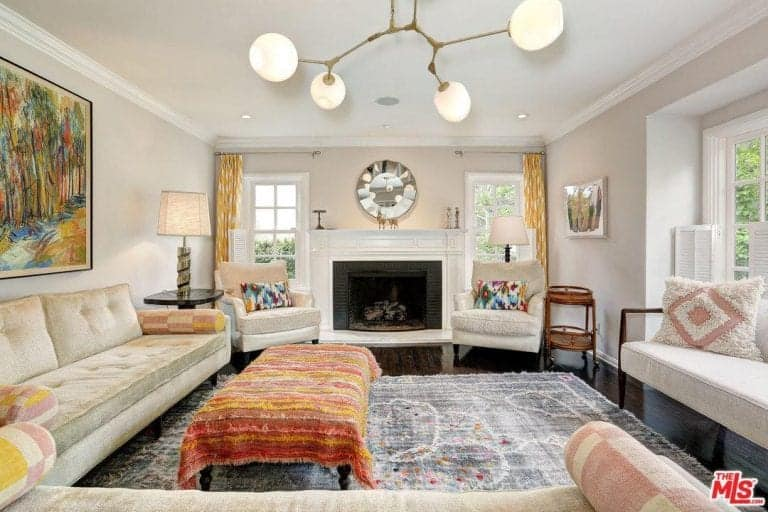 One of the living rooms offer stylish lighting and seats along with a stylish rug and a fireplace.