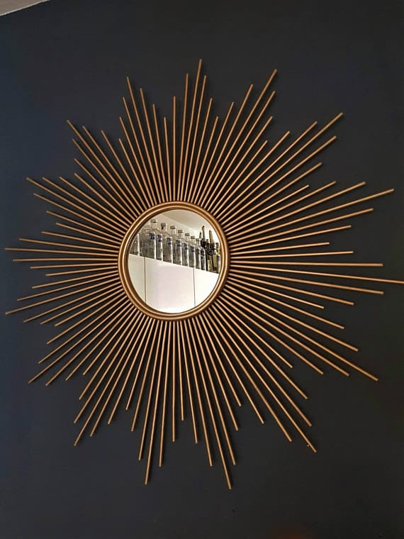Sun-shaped mirror wall art in Gold.