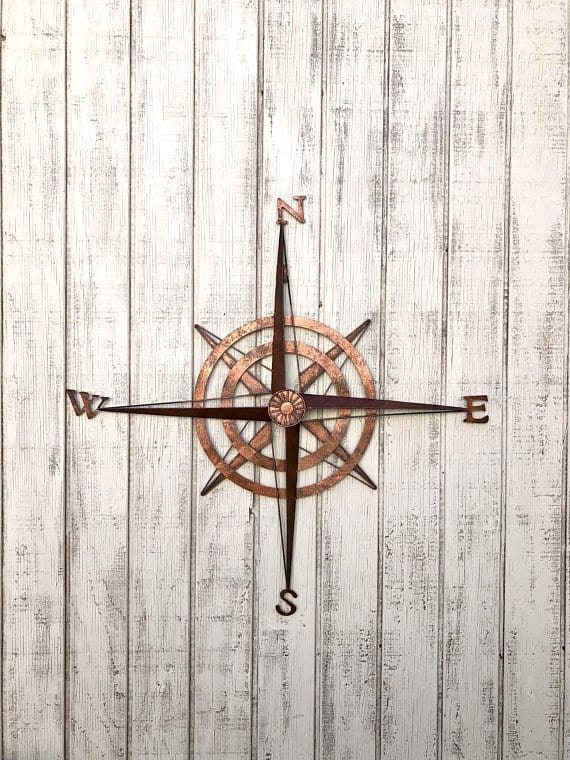 A dark gold, metallic compass as a wall decor.