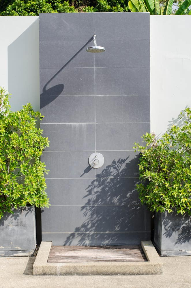 Modern outdoor shower with grey wall and highly set shower head surrounded by green plants.