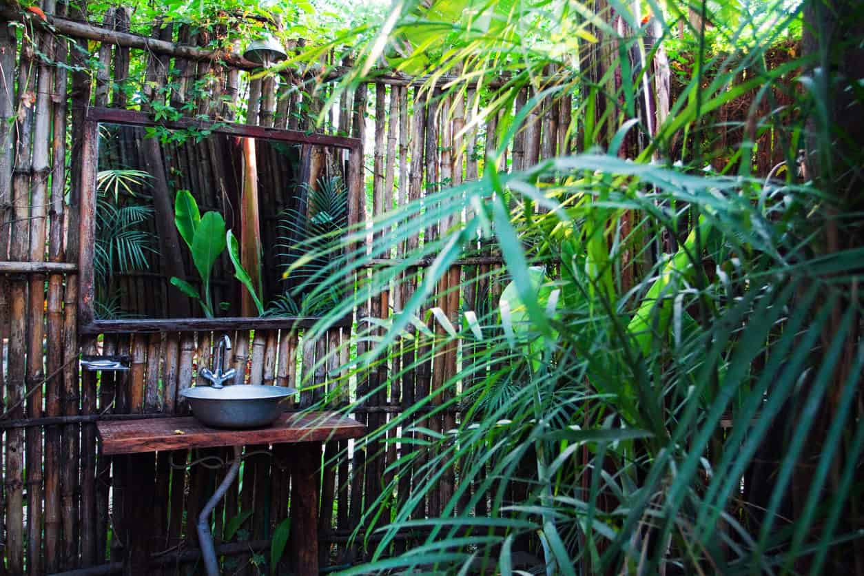 Open air outdoor bathroom with bamboo wall providing privacy. The area is surrounded by enchanting greens.
