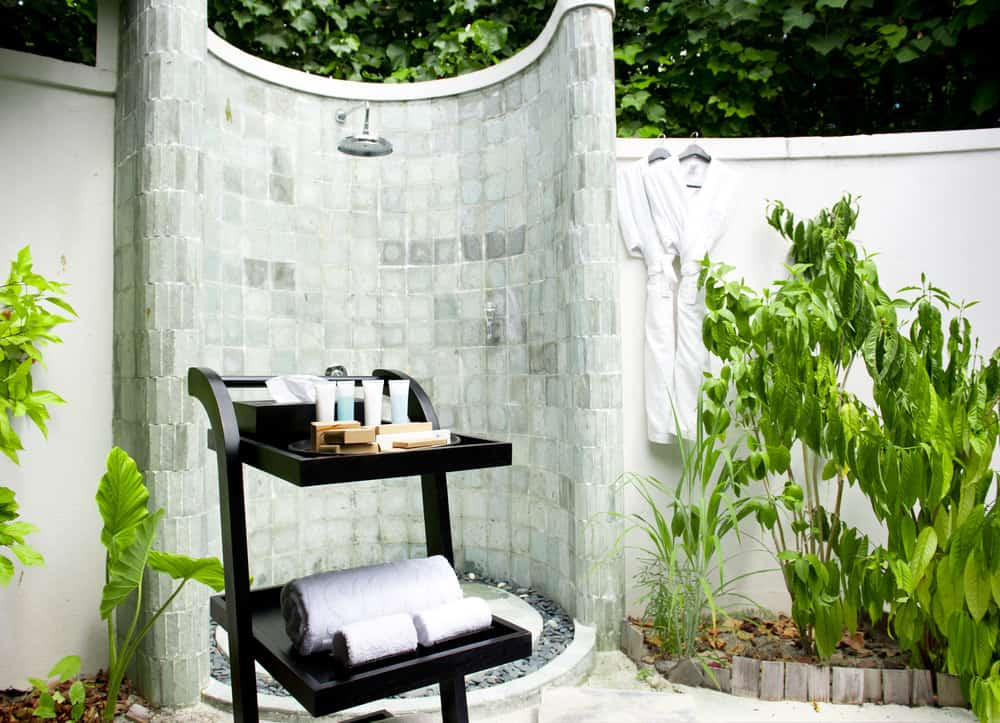A circular outdoor shower made in charming tiles set in the garden area of the property.
