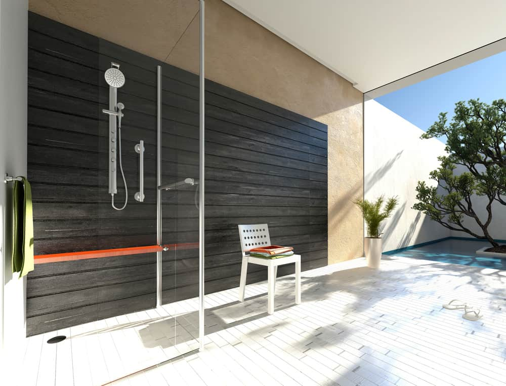 A walk-in shower made of glass set on the deck near the stunning pool of the house.
