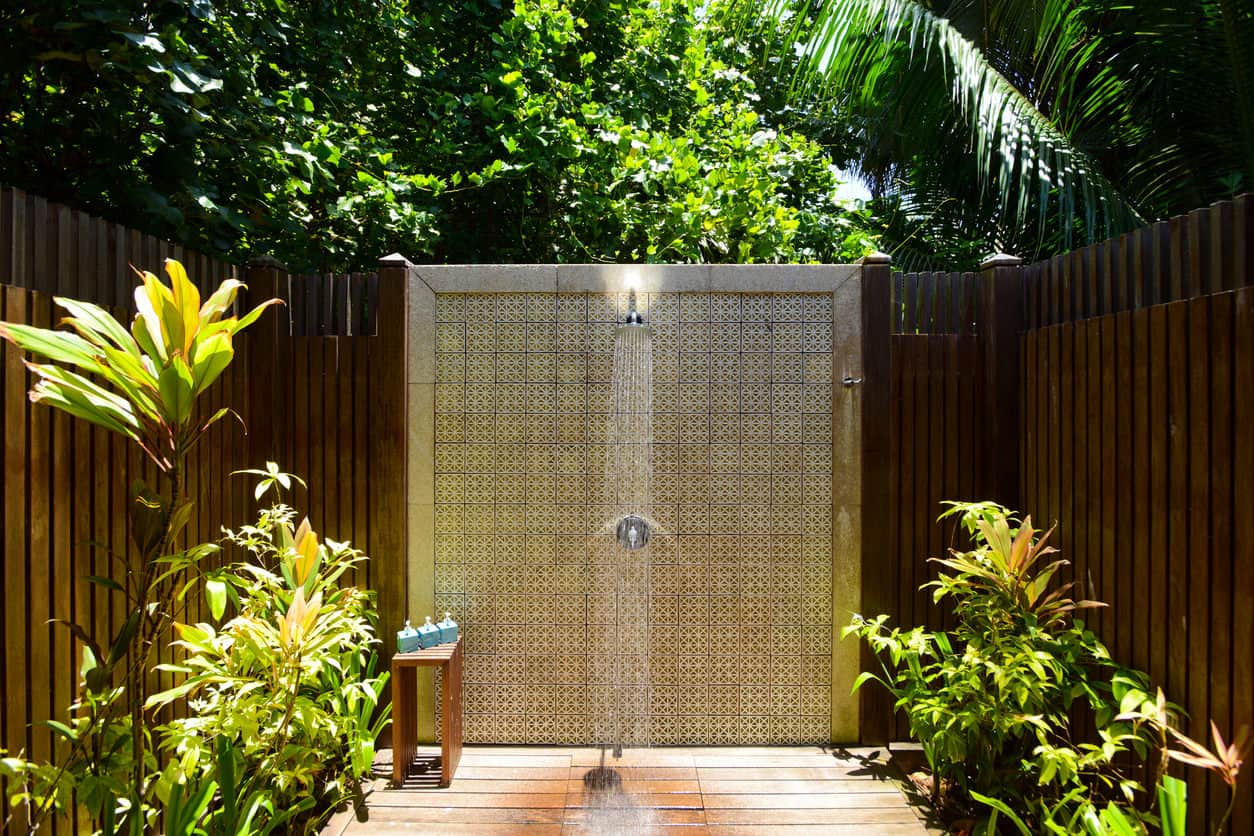A bewitching and serene outdoor shower with vegetation surrounding it for privacy.
