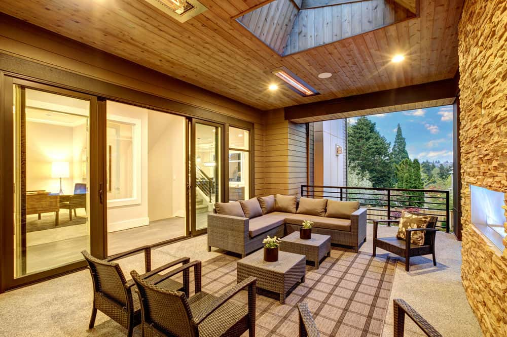 Stunning covered patio with recessed lighting and skylight and patio sectional sofa.
