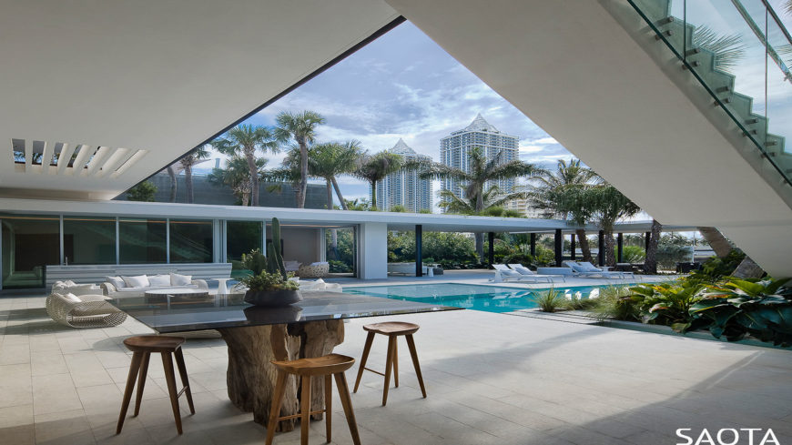 Modern mansion featuring a small dining table set and a cozy patio area near the swimming pool.
