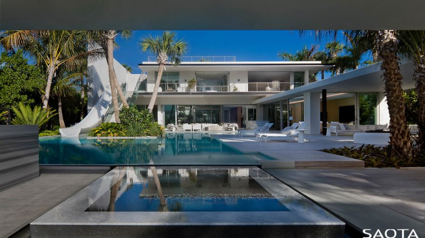 This home features an infinity pool with a slide. Multiple lounging spaces are on the side.
