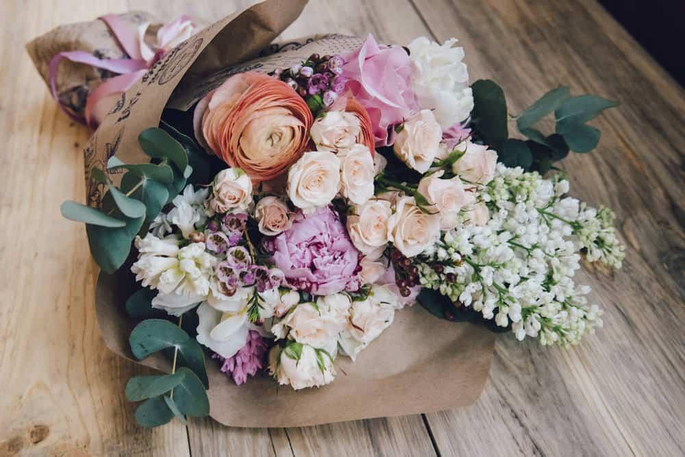 Beautiful flower arrangement of fresh white lilacs, roses, ranunculus, peonies, hyacinths and eucalyptus.
