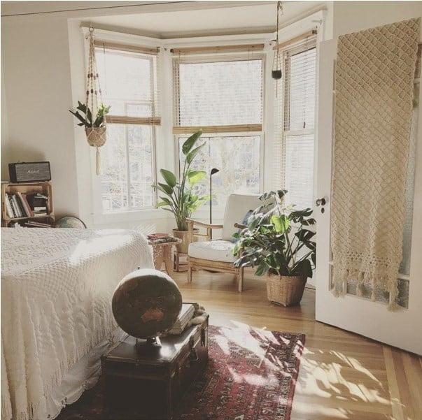 Primary bedroom with reading nook bay window and plenty of plants.