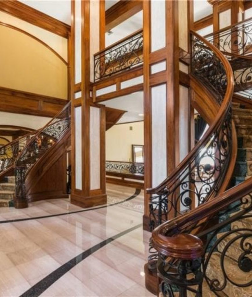 The home features a grand foyer with curved staircase and two-storey ceiling.