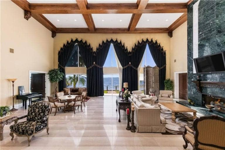 Spacious formal living room with an elegant sofa set and a large fireplace along with a dining nook and a piano, all under the stunning high coffered ceiling.