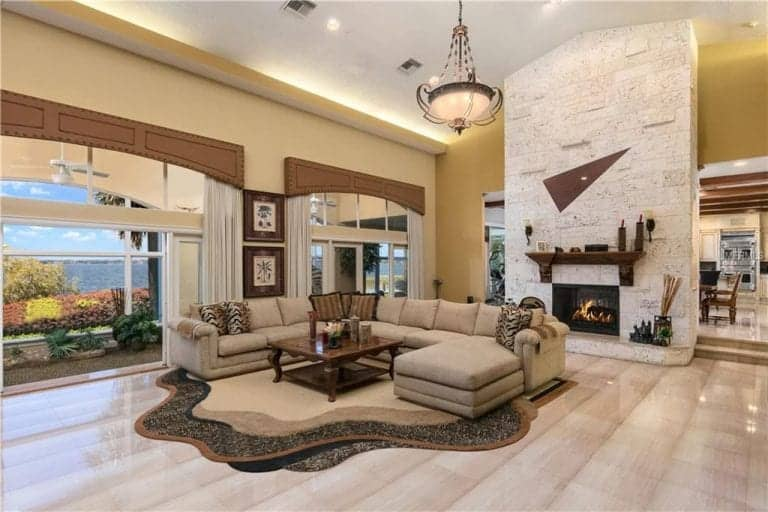 Large formal living room with a sparkling smooth flooring and a stunning ceiling with an elegant lighting. The sofa set looks perfect with the room's style.