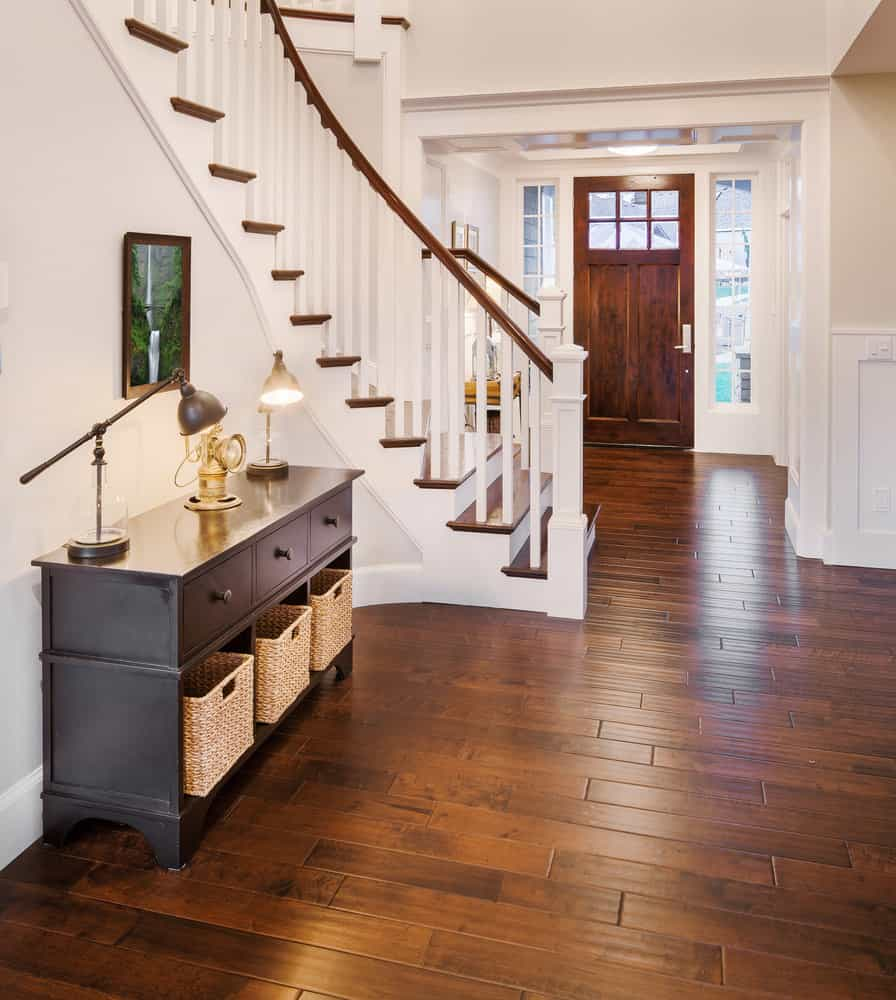 Foyer with winding staircase and medium wood flooring and foyer table against the wall