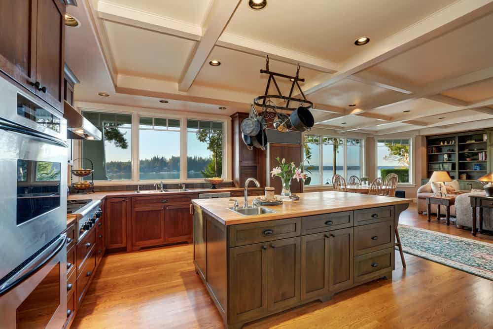 A great room with a stunning coffered ceiling. The kitchen features a handsome center island with a small space for a breakfast bar.