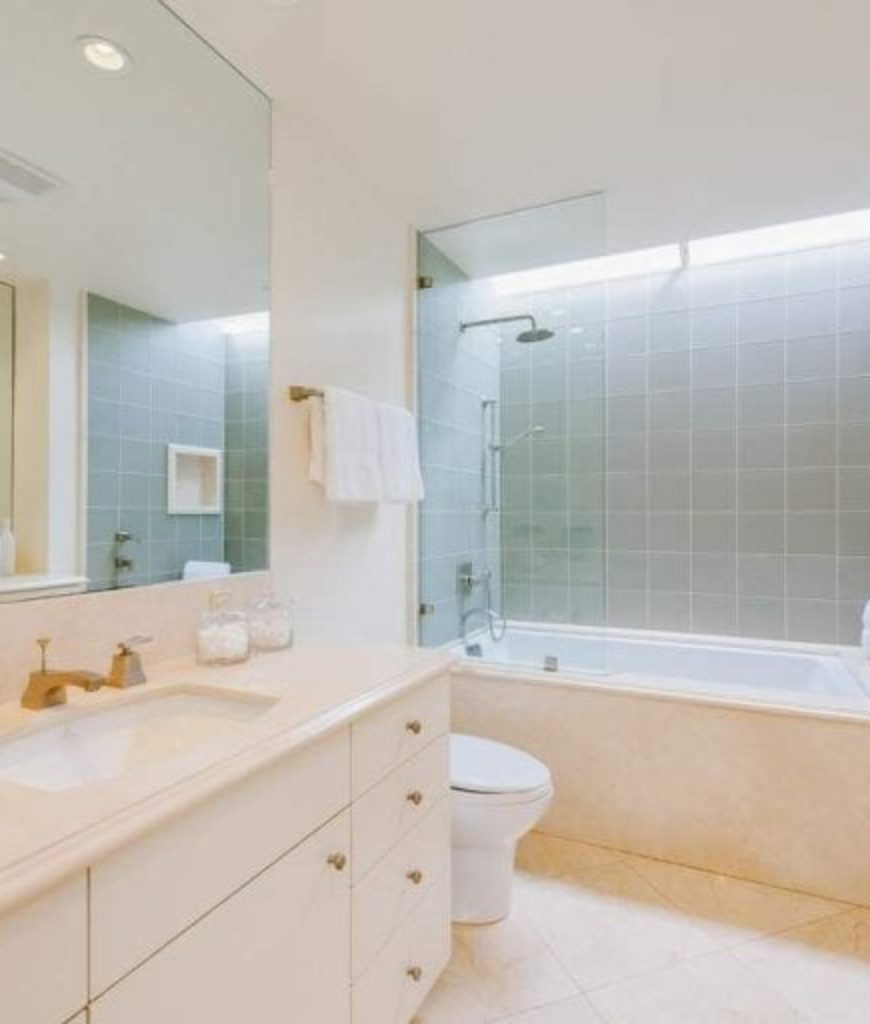 The bathroom is complete with shower and tub combo along with a single sink and recessed ceiling lights.