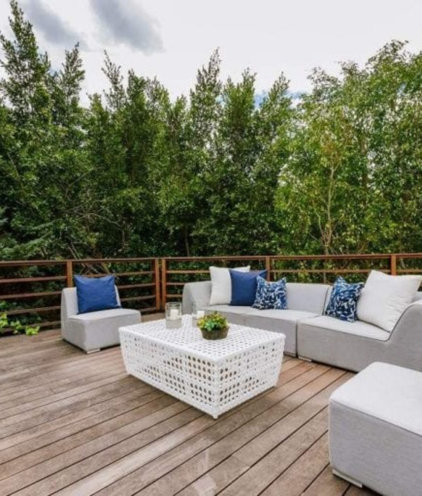 The deck offers a cozy set of seating lounge surrounded by healthy greens.