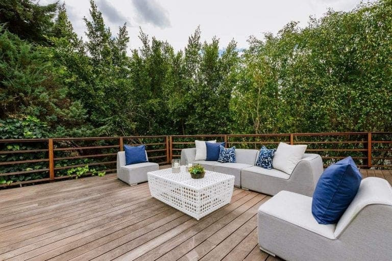This deck offers a comfortable sofa set surrounded by glamorous greenery.