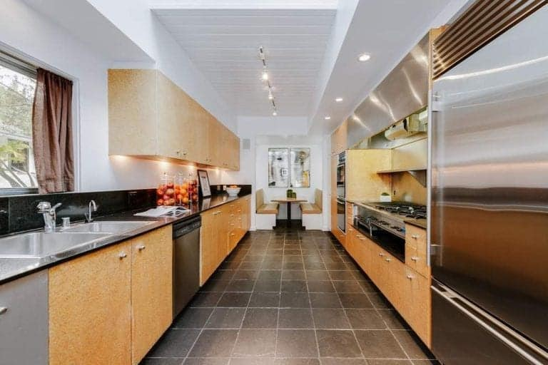 Galley kitchen with a dining nook at the far end showcasing beige built-in benches and a light wood dining table in the middle.