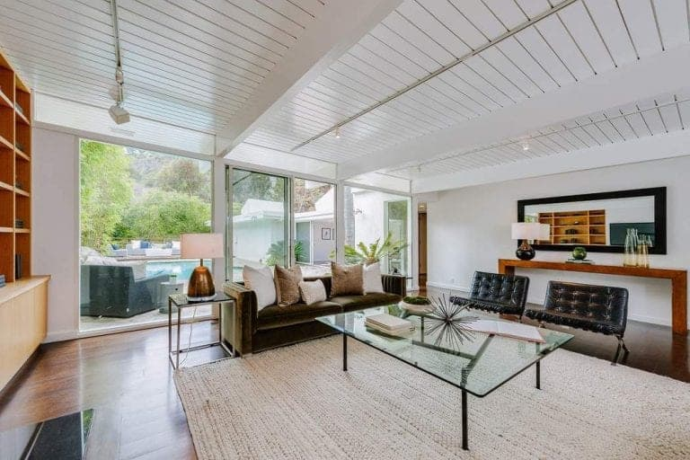 A glass top coffee table sits on a jute area rug in this living room with white shiplap ceiling and floor to ceiling glass slider that opens to the sparkling swimming pool.