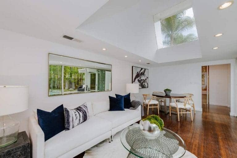 This living room features white sofa set matching the white walls and ceiling. There's a skylight as well, lighting up the space.