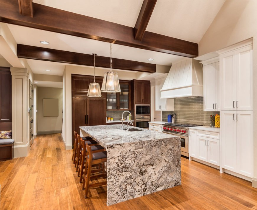 Large gray and white granite waterfall island in white kitchen with ceiling beams and hardwood flooring.