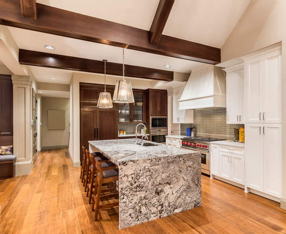 Gentil Large Gray And White Granite Waterfall Island In White Kitchen With Ceiling  Beams And Hardwood Flooring
