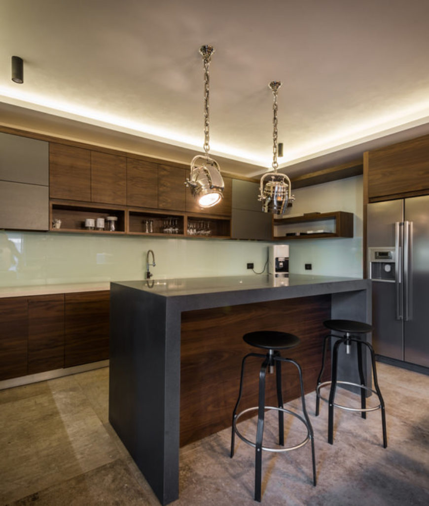 Modern dark brown kitchen with dark gray island surface that waterfalls down the ends of the island.
