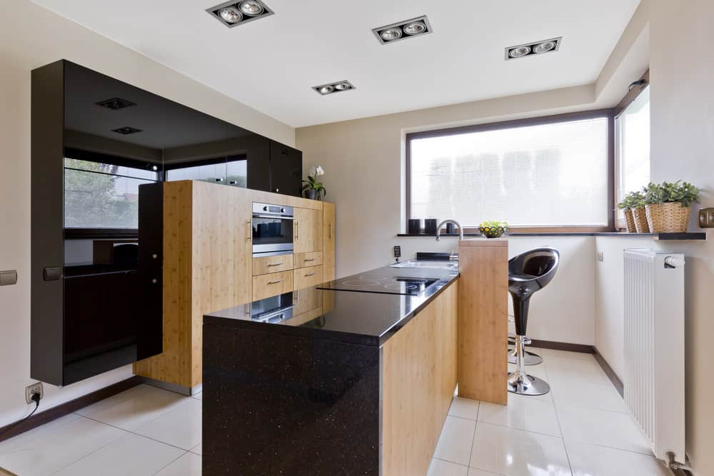 This modish kitchen has tiles flooring and white walls. The black shade, along with the narrow center island look so beautiful.
