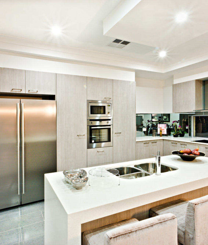 Stark white kitchen with stainless steel appliances with white island surface with waterfall effect.